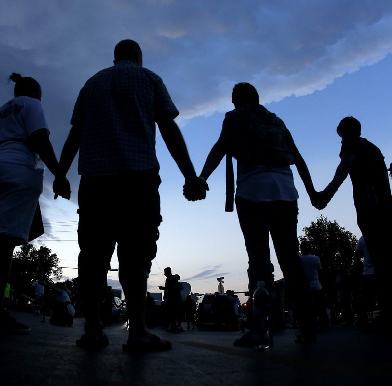 People stand in prayer after marching about a mile to the police station to protest the shooting of Michael Brown in Ferguson, Mo., in August.