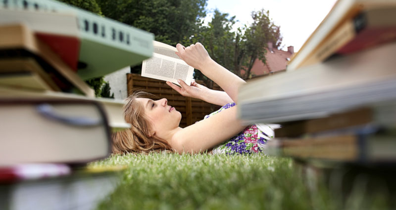 young woman lying on grass in garden reading books